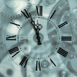 Old hours with figured arrows on mechanism blur background — Stockfoto
