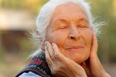 The elderly woman with closed eyes — Stock Photo