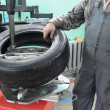 The car mechanician changes a tyre cover on an automobile wheel - Stock Photo