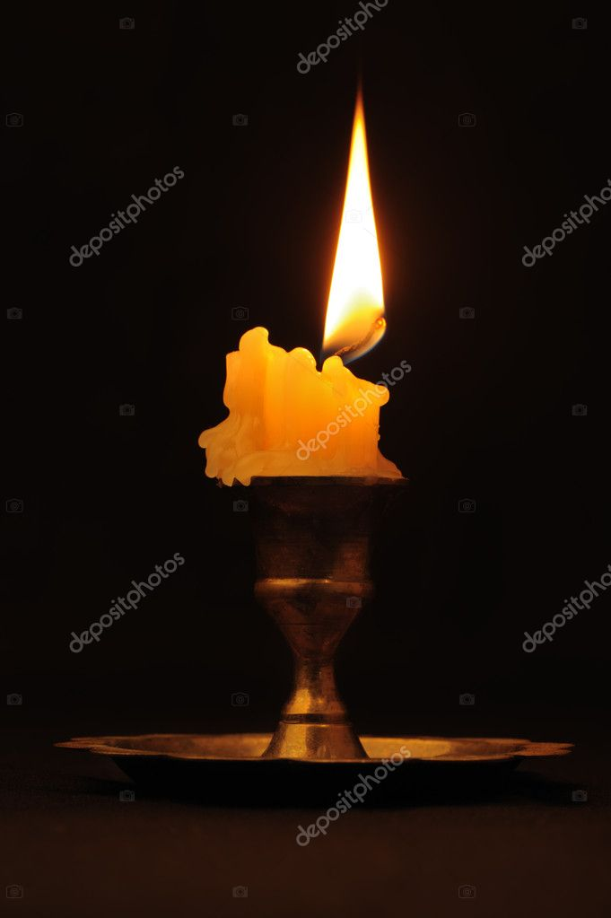 Burning candle. An ancient candlestick, a dark background — Stock Photo #7586647