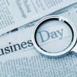 Loupe lies on the newspaper with title Business day. Blue toned — Stock Photo #7817348