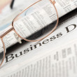 Eyeglasses lie on the newspaper with title Business day — Stock Photo #7817387