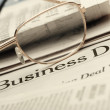 Eyeglasses lie on the newspaper with title Business day - Stock Photo