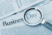 Loupe lies on the newspaper with title Business day. Blue toned — Stock Photo