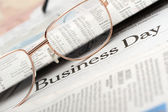 Eyeglasses lie on the newspaper with title Business day — Stock Photo