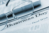 Eyeglasses lie on the newspaper with title Business day. Blue to — Stock Photo