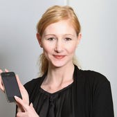 Young, smiling woman presented their smartphone — Stock Photo