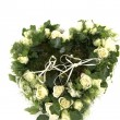 Wedding rings on a heart made ??of roses and ivy — Stock Photo