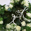 Stock Photo: Wedding rings on a heart of white roses