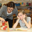 A teacher and pupil count together in schoo - Stock Photo