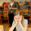 Stressed-out student in the school with a book in front of. — Stockfoto