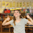 Hilarious girl at school shows thumb up — Zdjęcie stockowe