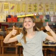 Hilarious girl at school shows thumb up — Stockfoto