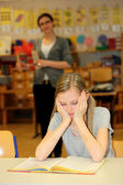Stressed-out student in the school with a book in front of. — Stock Photo