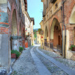 Old narrow street among ancient houses in Avigliana, Italy. - Stock Photo