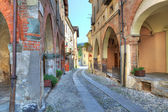 Old narrow street among ancient houses in Avigliana, Italy. — Foto de Stock