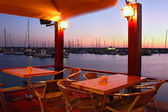 Outdoor restaurant on marina at evening. — Stock Photo