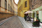 Old street with small hotel and outdoor restaurant in Prague. — Stock Photo