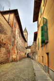 Narrow street among old houses in Saluzzo, Italy. — Stock Photo