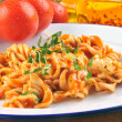 Stockfoto: Homemade pasta salad on a plate with fresh tomatoes in the backg