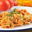 Homemade pasta salad on a plate with fresh tomatoes in the backg — Stockfoto