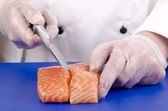 Female chef cuts salmon fillets with a kitchen knife — Stock Photo