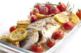 Baked sea bream with tomato, garlic and lemon slices — Stock Photo