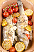 Two baked sea bass in a cassarolle with tomato and garlic — Stock Photo