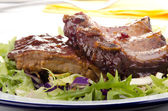 Barbecue spare ribs on a plate with fresh salad — Stock Photo