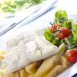 Cod fillet on french fries with salad and tomato — Stock Photo