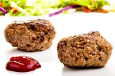 Homemade meatballs with ketchup and salad in the background — Stock Photo