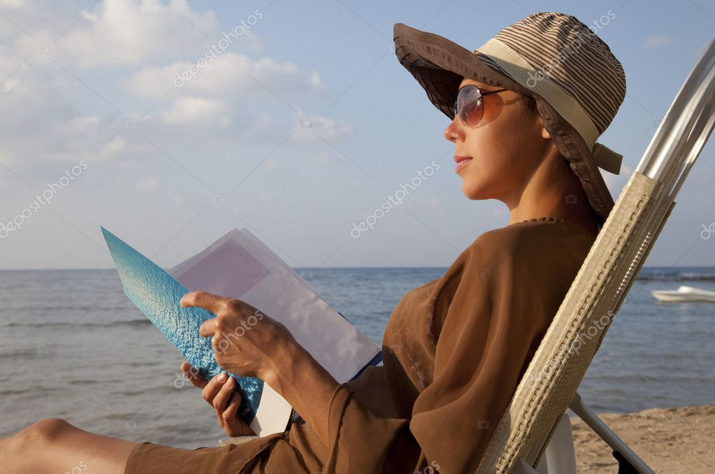 Woman reading book at beach and sitting in lawn chair  Stock Photo #7401783