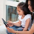 Mother and daughter reading electronic book — Stockfoto