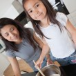 Mother and daughter Baking together - Stock Photo