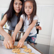 Stock Photo: Mother and child making cookies