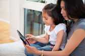 Mother and daughter reading electronic book — 图库照片