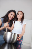 Portrait of mother and daughter in kitchen — Stok fotoğraf