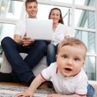 Child on Floor - Parents Using Laptop — Stock Photo