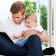 Man Using Digital Tablet while Holding Child — Stock Photo