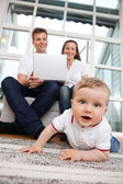 Child on Floor - Parents Using Laptop — Stock Photo