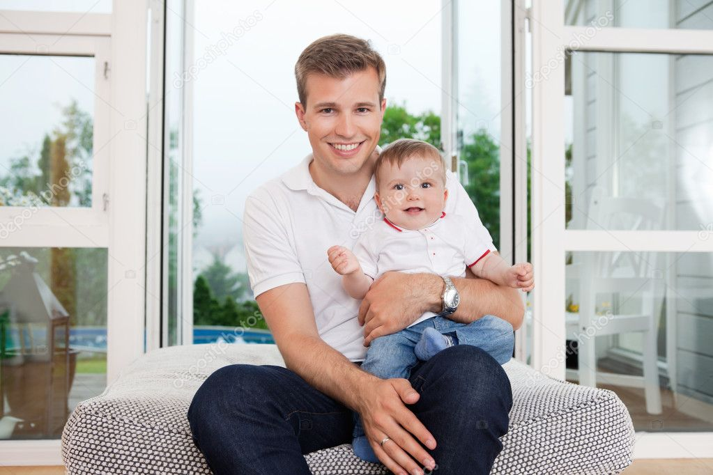 Portrait of smiling young father with child sitting on couch — Stock Photo #6815406