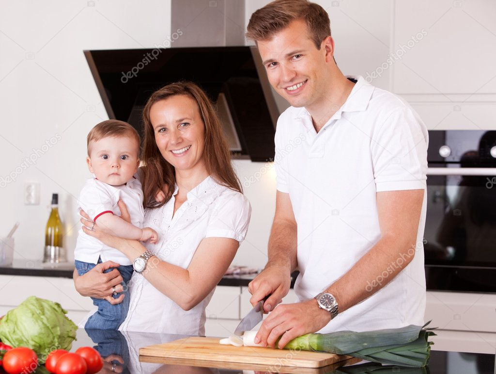 Portrait of a happy family at home in the kitchen preparing a meal — Foto Stock #6815533