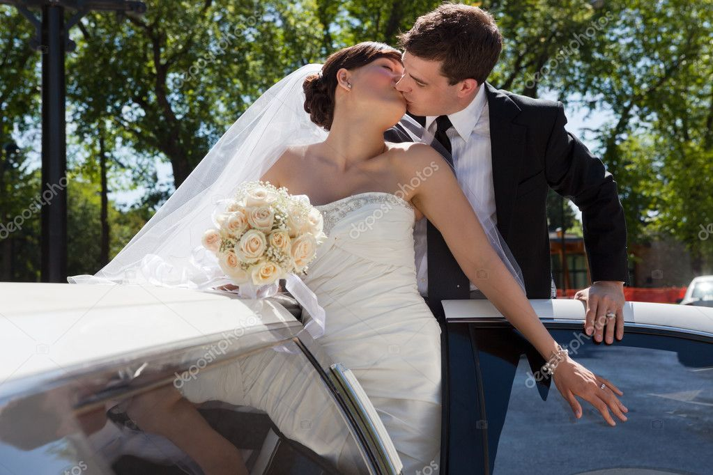 Passionate married couple kissing while standing in limo  Stock Photo #6959648