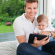 Man using digital tablet with child — Stock Photo