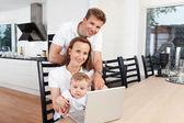 Happy family with laptop — Stock fotografie