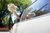 Bride waving hand holding bouquet — Stock Photo
