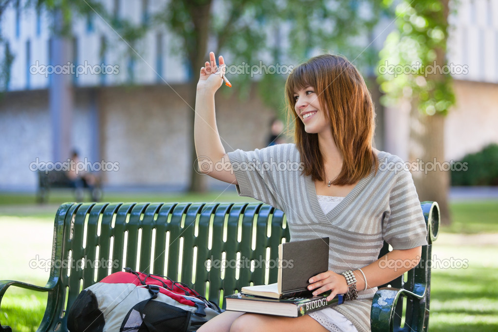 Young smiling college girl waving hand to person outside of image — Stock Photo #6989494