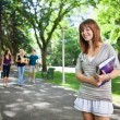 College girl standing with a book — Stock Photo