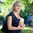 Stock Photo: Smiling college girl with book and bag