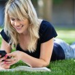 Happy young girl using cell phone - Stock Photo